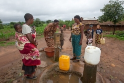 Deja Borders pumps water from a borehole while villagers look on.