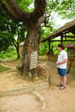 A student contemplates the plaque at The Killing Tree at Phnom Penh, Cambodia.