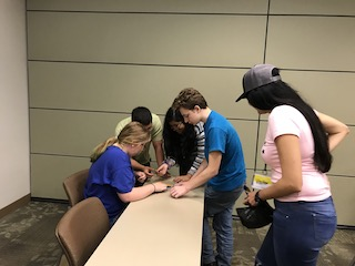 Upward Bound students complete a puzzle of the Colombian flag, while supervised by Fulbright TEA participant Pamela