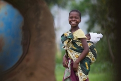 A young girl in the Mchezi Village smiles on her way home from school as she carries her younger sibling on her back.