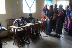 Students visit a community-based organization's tailoring shop where women are taught how to sew in hopes they will learn the trade.