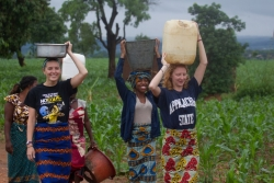 Ellen Mason, Alex White and Anja Wicker carry water from the well back to their hosts' home.